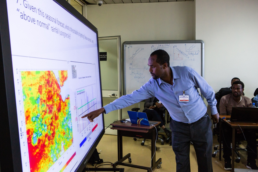 An Ethiopian workshop participant in a blue collared shirt with a ID tag clipped to his shirt points to a large screen with a weather map and accompanying graph. Other seated participants look on from the background.  A participant shares the result of his small group's work on an exercise during a training held at the National Meteorological Agency in Addis Ababa in October of 2018. Photographer Elisabeth Gawthrop, ACToday/IRI.