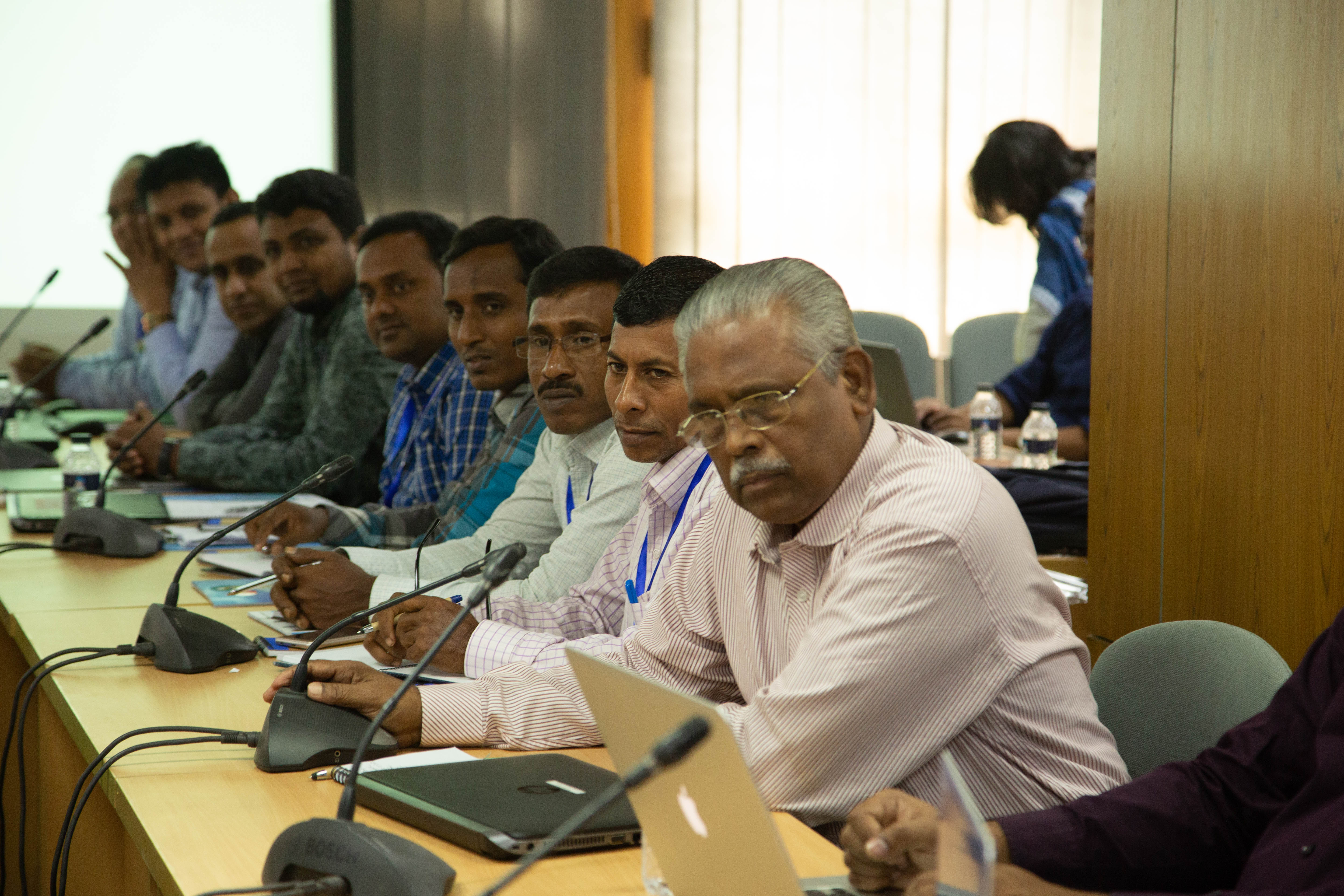 A row of Bangladeshi men of varying ages sit at a conference table with microphones and notepads in front of them. They are participants listening to a presentation during a training held at the Bangladesh Meteorological Department in Dhaka in October of 2019. Photographer Jacquelyn Turner, ACToday/IRI.