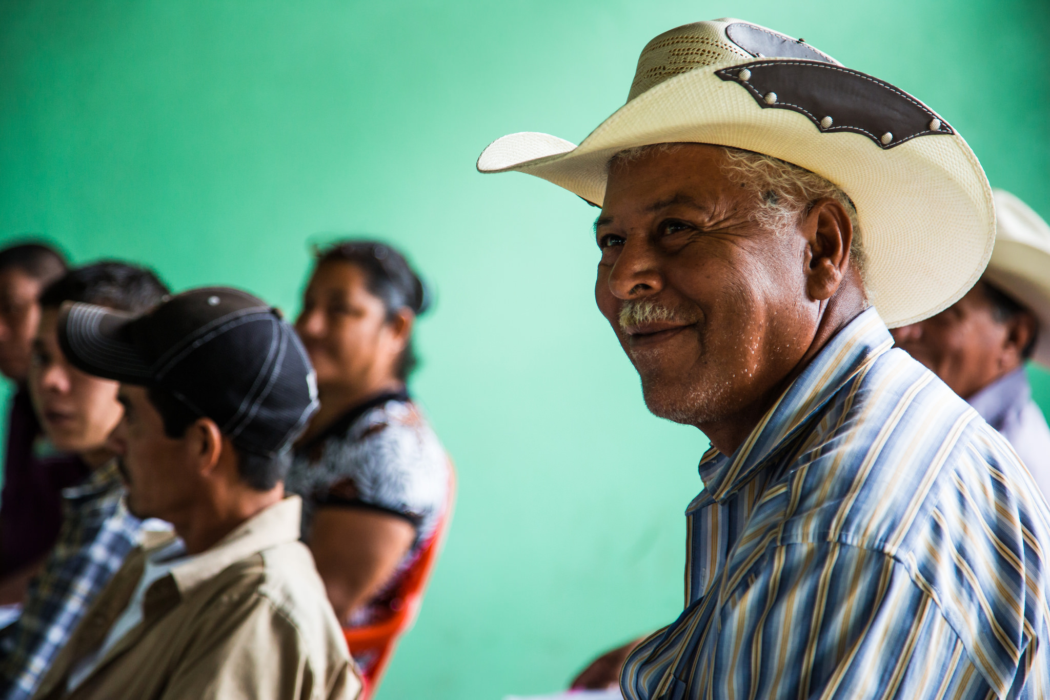 A male Honduran farmer wearing a blue and yellow striped collared shirt and cowboy hat is in focus in front of other farmers also seated in plastic chairs in front of a green wall in an outdoor classroom space in southern Honduras.