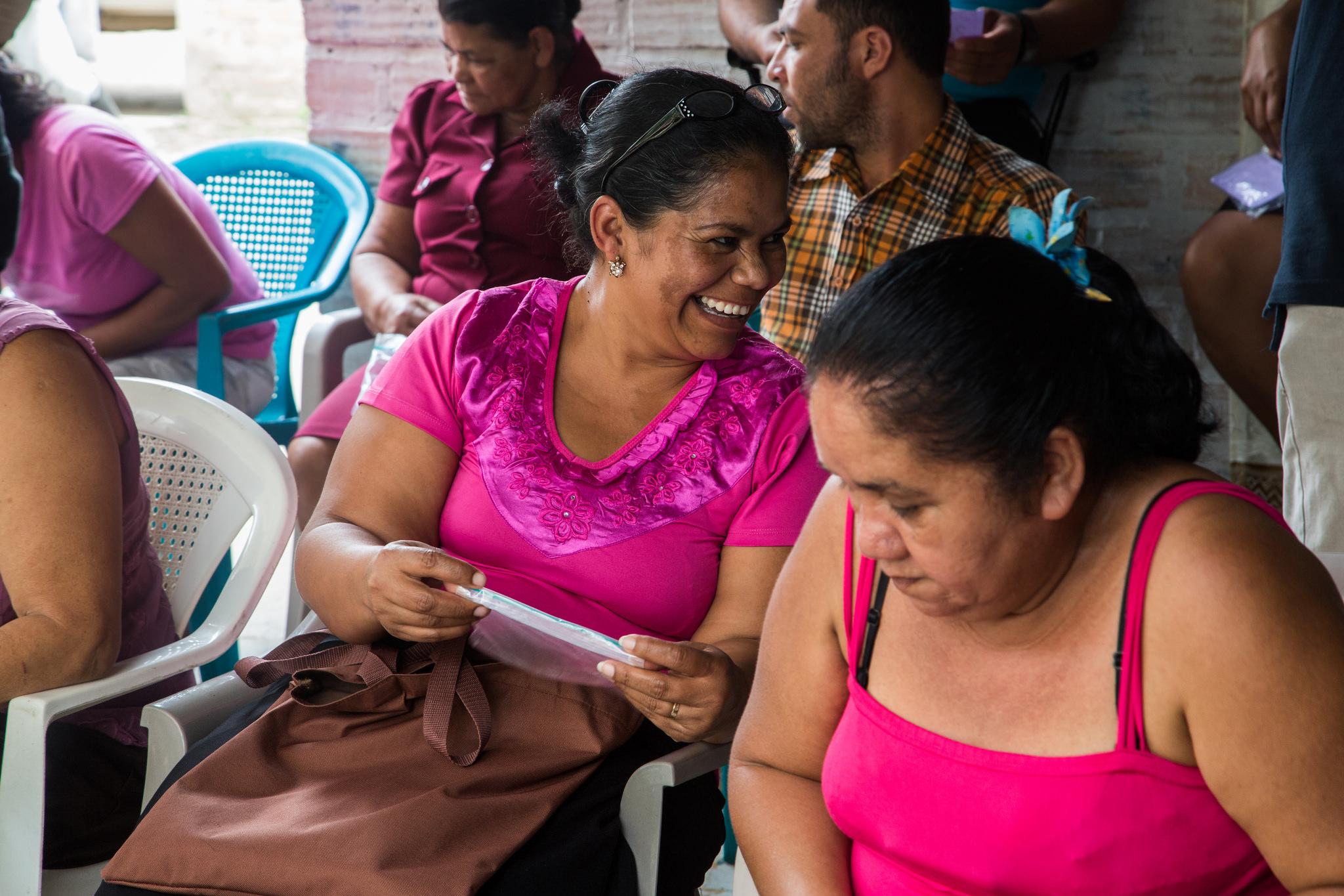 A Honduran woman farmer in a magenta shirt laughs to an unseen companion while holding a strip of white paper. She is surrounded by other farmers seated in plastic chairs during an index insurance game session in southern Honduras.