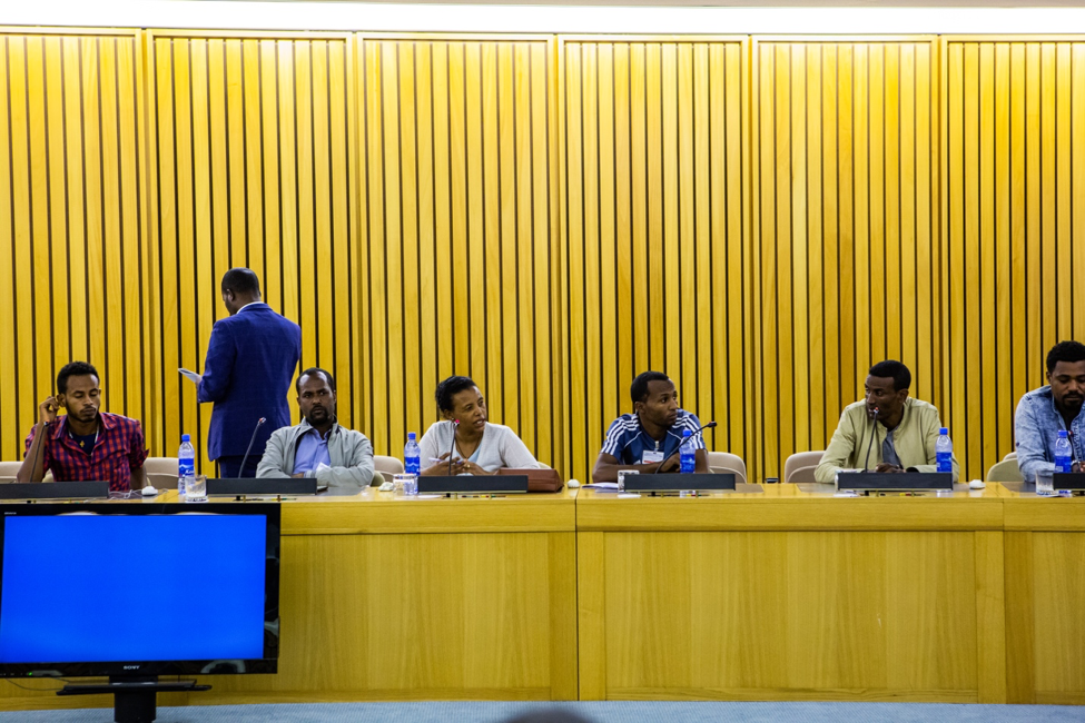 Eneye Assefa, third seated from the left, speaks during the closing ceremony of the training. Wood paneling stretches up the wall behind the panel of six Ethiopian participants sitting at the panel-like table. Each has a plastic water bottle and microphone in front of them. Photographer Elisabeth Gawthrop, ACToday/IRI.