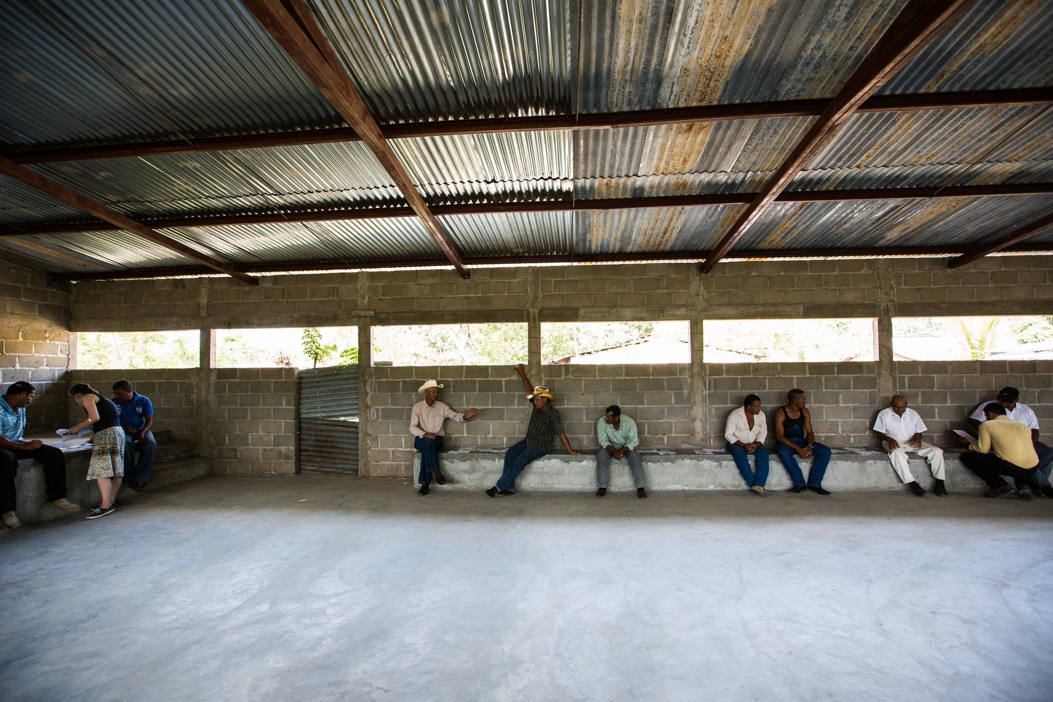 The camera captures a scene inside a community shelter in southern Honduras. In one corner, a index insurance educator bends over maps with two Honduran farmers. Several other farmers are seated across the back wall along a concrete bench, some wearing cowboy hats.