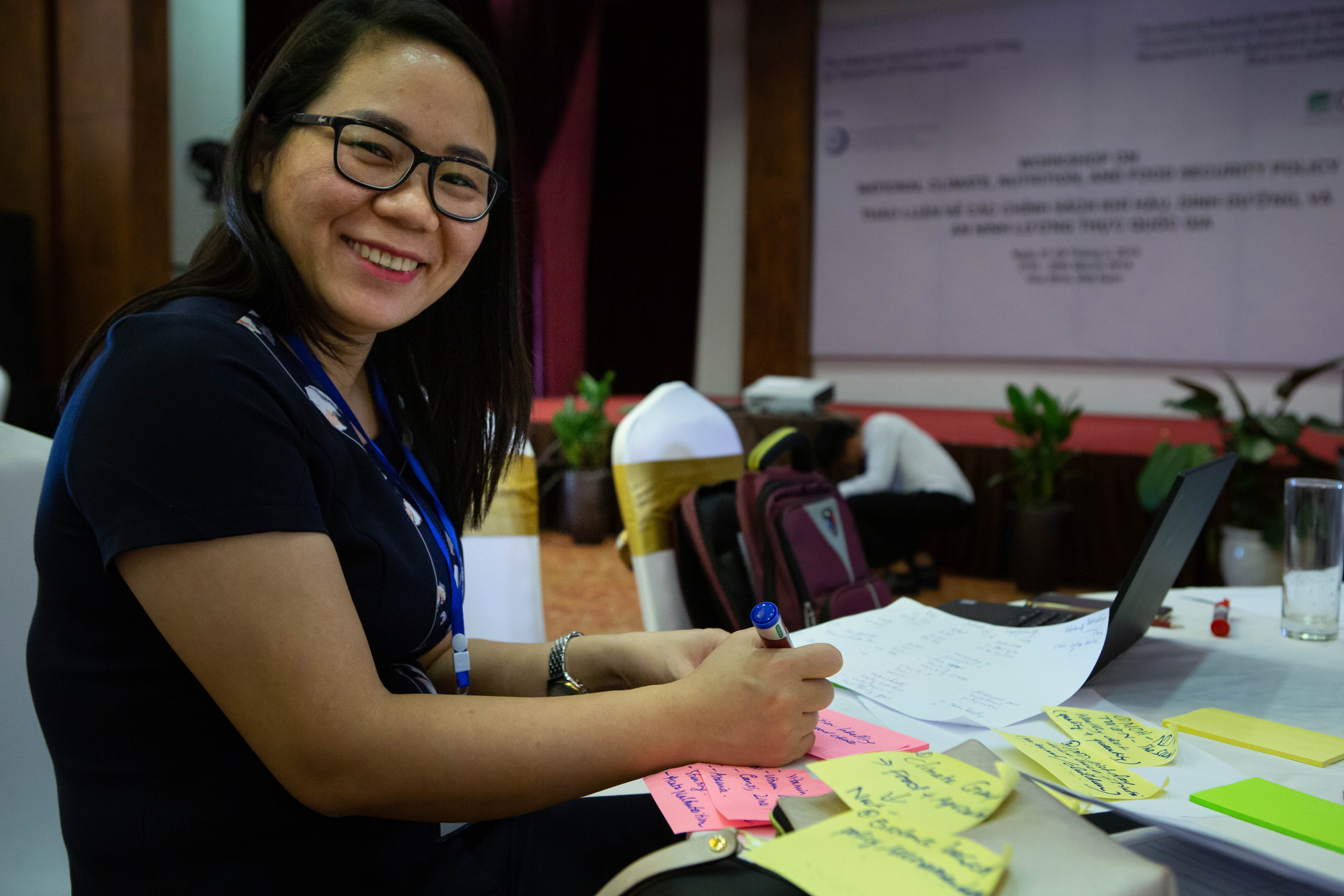 Dr. Truong Mai from the National Institute of Nutrition writes notes for a group activity where participants identified challenges to achieving their objectives for UN Sustainable Development Goal 2.